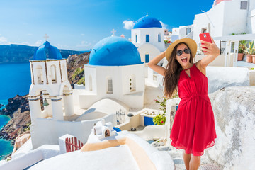 Wall Mural - Santorini tourist girl on cruise holiday taking selfie photo with phone at famous three domes church, European tourism attraction in Greece. Asian woman on vacation.