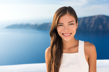 Wall Mural - Beautiful Asian young woman smiling portrait in sunshine. Gorgeous Chinese Caucasian model in summer outdoors, Europe travel destination, luxury Santorini Greece getaway.