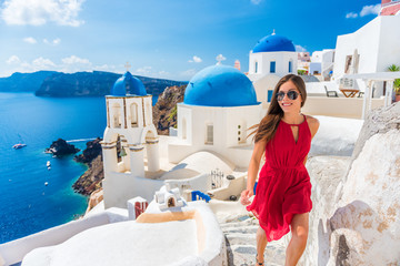 Fototapete - Europe summer vacation tourist woman walking in Oia city at three blue domes church, Santorini, Greece. famous cruise travel destination, Mediterranean Sea.