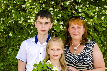 Mom and two children of teenagers are standing by the bush of jasmine.