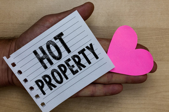 Text sign showing Hot Property. Conceptual photo Something which is sought after or is Heavily Demanded Man holding piece notebook paper heart Romantic ideas messages feelings