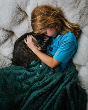 girl cuddling her per cat on the couch