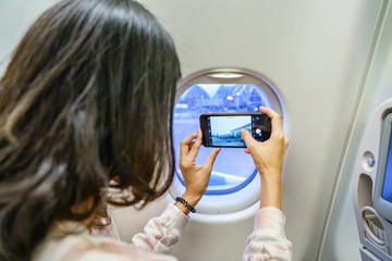 Travel and technology. Young woman in plane taking photo on her smartphone while sitting in airplane seat. Focus on phone.