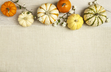 Colorful yellow, orange and white minature pumpkins squash on rustic wood and burlap background. Fall autumn table decorations horizontal seasonal banner border.