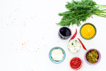 Different dip sauce in bowls near chili pepper and greenery. Ketchup, mayonnaise, mustard, soy sauce, barbecue sauce, pesto, mustard, sour on white background top view space for text