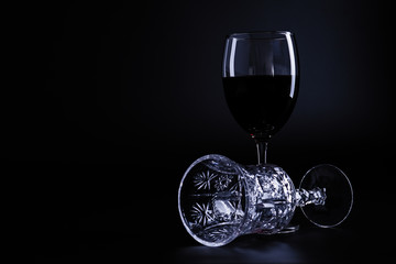 Silhouette of two wine glasses one with red wine one empty and lay down on black background