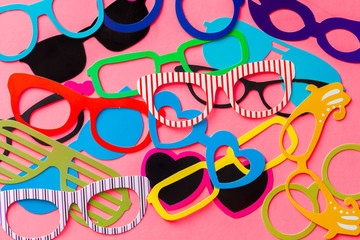 Collection of colorful photo booth eyeglasses on pink background