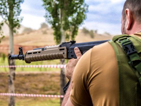 A man shoots a machine gun
