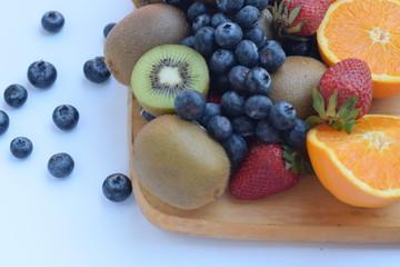 mixed fruit on wood cut board white background isolated,kiwi,blueberry, strawberry, navel orange