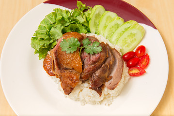 German pork knuckle with rice, vegetable and fruit served with sauce on wooden table.