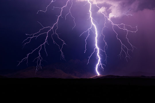 Lightning bolt strike on a mountain during a storm.
