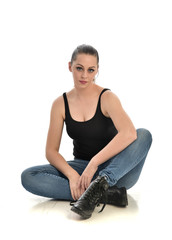 full length portrait of brunette girl wearing black single and jeans. seated pose. isolated on white studio background.