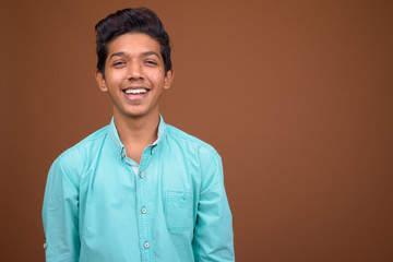 Young Indian boy wearing blue shirt looking smart against brown