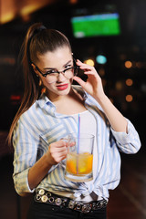 a beautiful young girl with glasses is holding a mug with beer or a beer orange cocktail in front of a bar or a pub