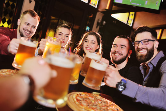 group or company of friends - young guys and girls eat pizza and drink beer in a bar, communicate and laugh.