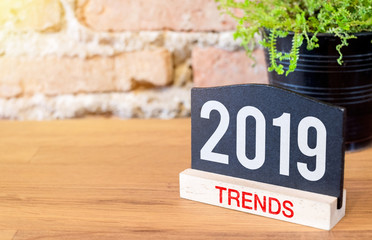 New year 2019 trends on blackboard sign and green plant on wood table at brick wall.Business plan for next year.