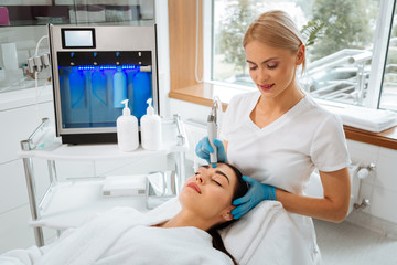 Professional skills. Professional skilled cosmetologist standing near the client while doing hydrafacial procedure
