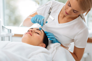 Professional facial treatment. Smart nice cosmetologist looking at the clients face while doing hydrafacial procedure