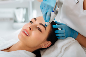 Rejuvenation of skin. Delighted nice woman smiling while enjoying hydrafacial procedure