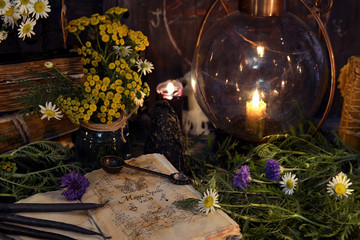 Still life with retro lamp, old book, black candles and healing herbs with flowers. Mystic background with ritual esoteric objects, occult, fortune telling and halloween concept