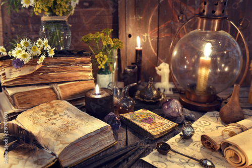 Wall mural Still life with old-fashioned lamp, magic witch books, tarot cards and old papers. Mystic background with ritual esoteric objects, occult, fortune telling and halloween concept