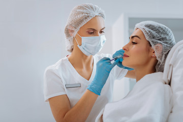 Skin renewal. Professional female cosmetologist standing near her client while doing a beauty injection for her