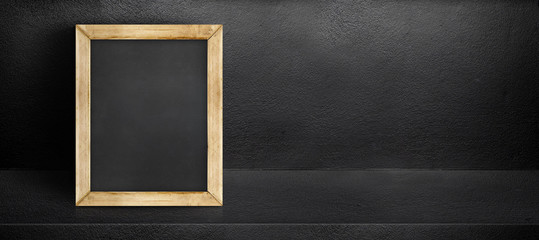 Blank blackboard leaning at black interior cement room background,banner mock up template for display of design,leave side space for adding text for advertising.