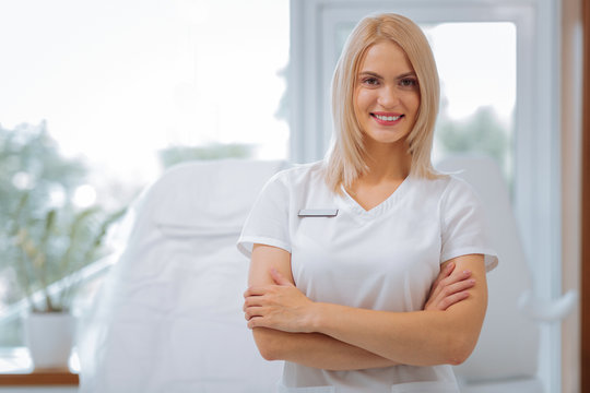 Favourite job. Delighted positive woman smiling to you while working as a cosmetologist in the clinic