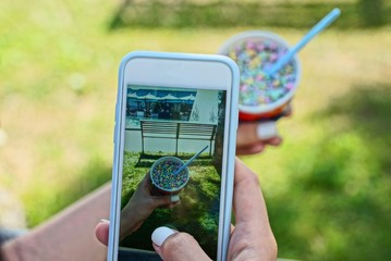 smartphone in the hands of a girl doing a photo of a colored ice cream in a cup outside in the park