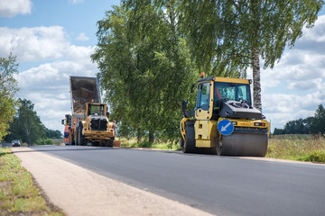 Road construction workers repairing highway road on sunny summer day. Loaders and trucks, heavy vibration roller compactor with arrow road sign on newly made asphalt. Work inspection with drone
