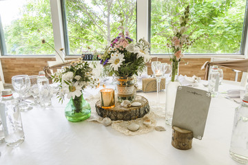 Round wedding table with forest theme, decoration, plates, forks, and glasses.