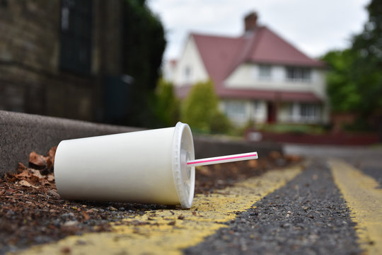 Discarded drinks container lying at the edge of an urban street with car in the distance