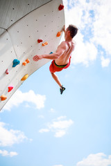 Photo from bottom of young athletic man exercising on wall for climbing against blue sky with clouds