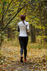 Photo from back of young woman running through autumn park