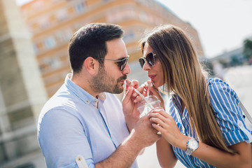 Young couple in love drinking juice, outdoor
