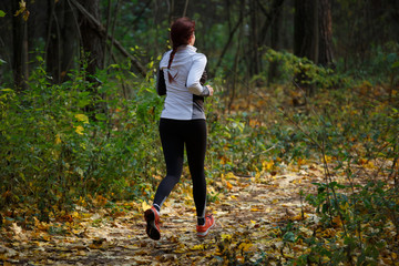 Image from back of woman in sports clothes on run at park
