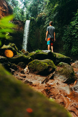Wall Murals Fantasy Landscape Low angle shot of young man standing near a waterfall in forest and looking away. Male hiker enjoying in the nature