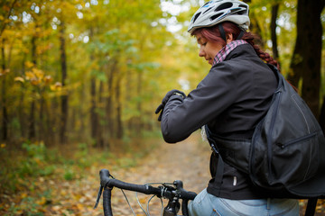 Photo of smiling brunette in helmet sitting on bicycle in autumn