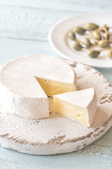 Camembert with capers on the wooden board