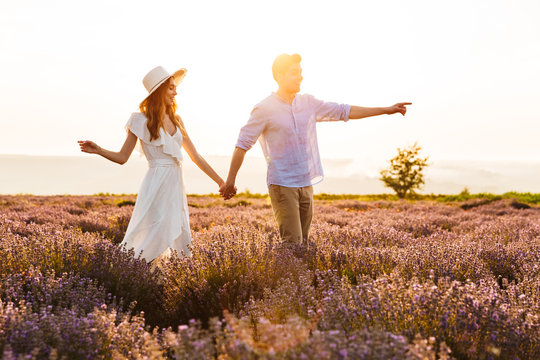 Photo of happy young man and woman dating, and walking together outdoor in lavender field
