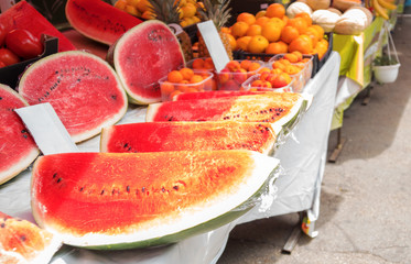 Market stand with watermelons and other fruits.