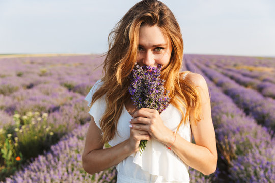 Photo of happy young woman in dress holding bouquet with flowers, while walking outdoor through lavender field in summer