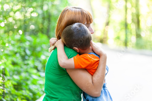 Beautiful woman and her  little son trembling and strongly embracing, on city park background. Summer portrait of mother and son on Mother's Day.