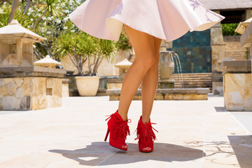 Woman in skirt and red high heel shoes