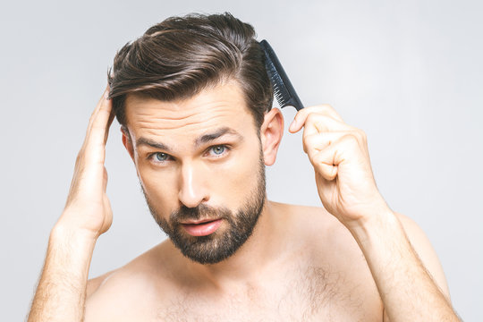 Portrait of handsome young man combing his hair in bathroom. Isolated over grey background.