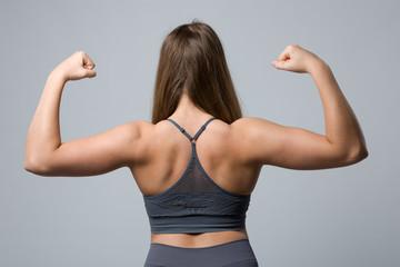 Rückenansicht einer jungen Frau im Sportdress die die Armmuskeln anspannt