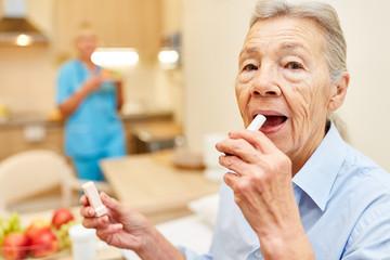 Senior Frau cremt ihre Lippen ein