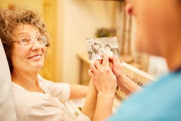 Pflegekraft zeigt Frau mit Demenz ein Foto