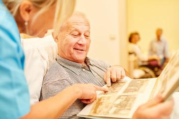 Senior Mann mit Demenz betrachtet Fotos