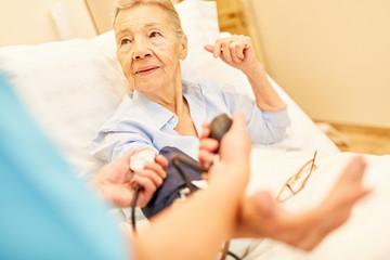 Kontrolle des Blutdrucks bei Senior Frau